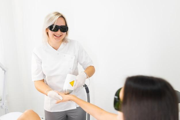 O mestre de depilação remove o cabelo da mão feminina da cliente