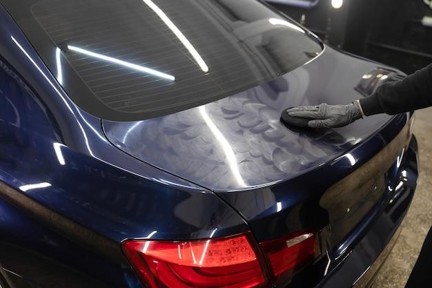 O mestre de detalhamento aplica cera de polimento na carroceria do carro.