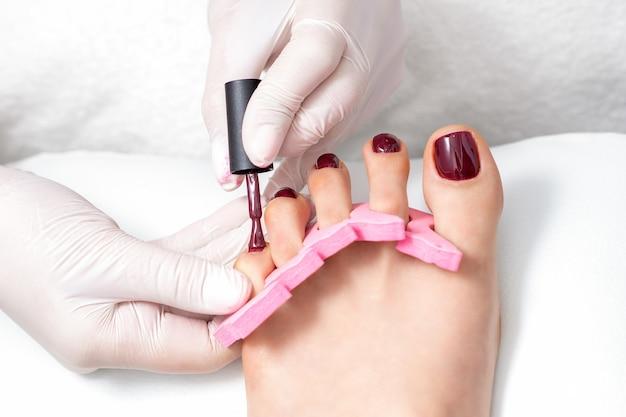 O mestre de manicure está pintando nas unhas dos pés femininos com esmalte marrom com pincel e usando luvas brancas