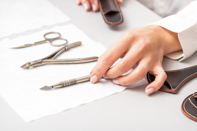 O mestre de manicure mostra o conjunto de manicure em uma toalha na mesa em um salão de beleza