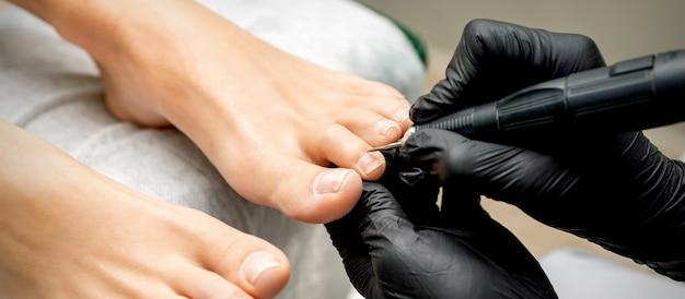 O mestre de pedicure remove a cutícula dos dedos dos pés de uma mulher usando unhas elétricas profissionais em um salão de beleza