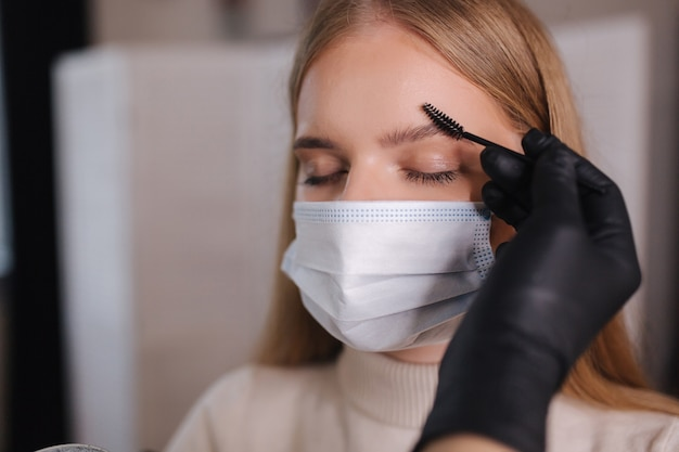 O mestre de sobrancelha e maquiagem em máscara protetora dá forma para puxar com uma pinça
