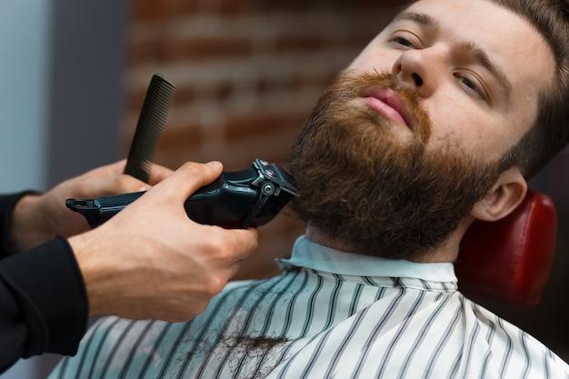 O mestre do barbeiro corta a barba