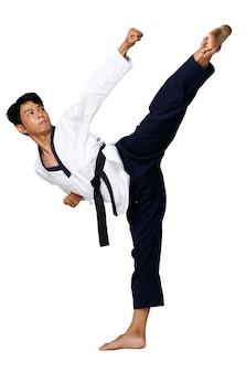 O mestre do esporte de taekwondo pratica poses de karatê. o instrutor usa o uniforme tradicional e mostra o poomsae kick agindo sobre um fundo branco isolado de corpo inteiro