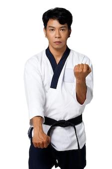 O mestre do esporte de taekwondo pratica poses de karatê. o instrutor usa o uniforme tradicional e mostra o poomsae punch agindo sobre um fundo branco isolado com metade do corpo