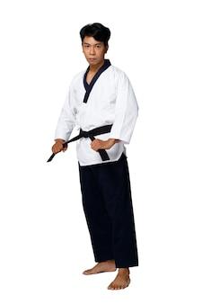 O mestre do esporte de taekwondo pratica poses de karatê. o instrutor usa uniforme tradicional e mostra poomsae agindo sobre fundo branco isolado de corpo inteiro