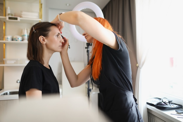 O mestre do salão de beleza feminino pinta as sobrancelhas para uma mulher com lápis cosmético.