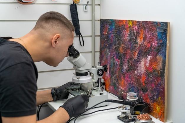 O mestre examina a microplaca através de um microscópio em um smartphone desmontado