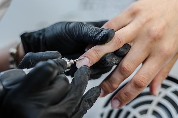 O mestre faz manicure de hardware no salão de beleza