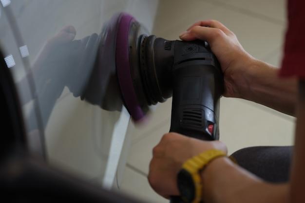 O mestre faz o polimento da carroceria do carro com arranhões e arranhões, close-up