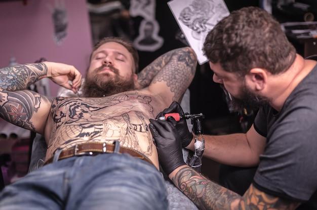 O mestre faz uma tatuagem no estúdio.