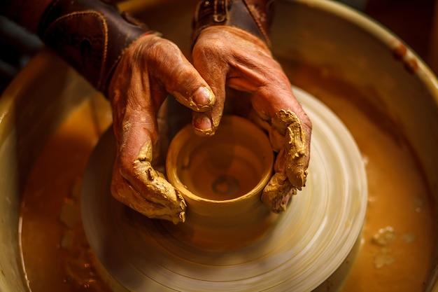 O mestre forma uma taça de barro na roda de um oleiro.