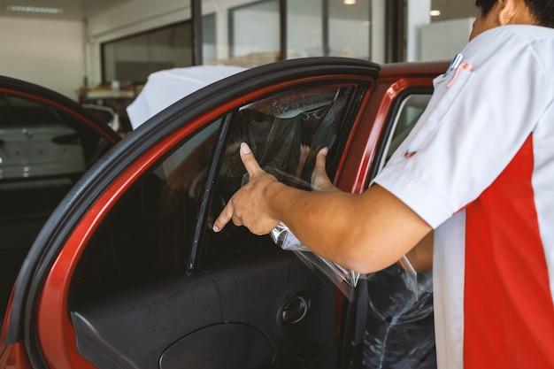 O mestre instala um filme colorido para o vidro do carro com foco suave
