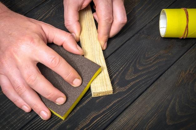 O mestre lustra a placa de madeira com uma ferramenta abrasiva