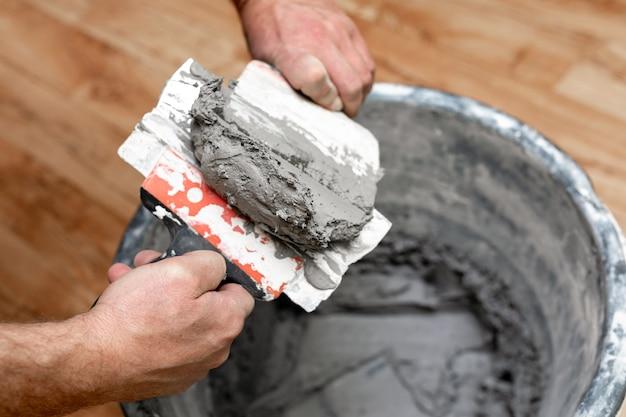 O mestre mistura o gesso em um balde.