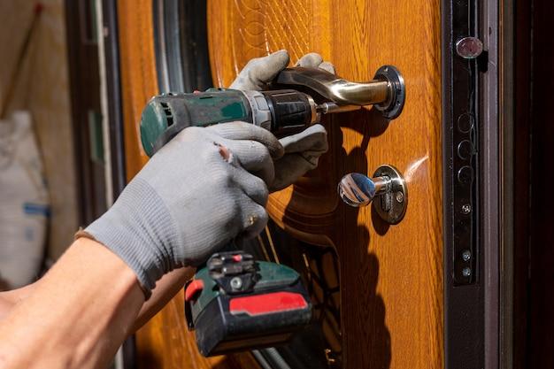 O mestre operário instala uma fechadura na porta da frente. portas de metal com revestimento de polímero.