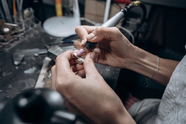 O mestre processa o metal valioso na oficina em casa