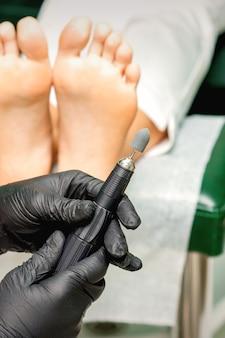 O mestre quiropodista prepara a máquina de lixar para os pés antes do tratamento de limpeza dos pés e dedos dos pés em um salão de beleza