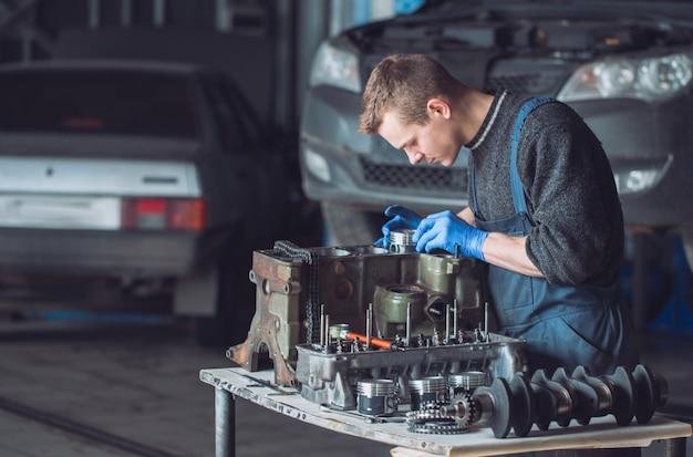 O mestre recolhe um motor reconstruído para o carro.