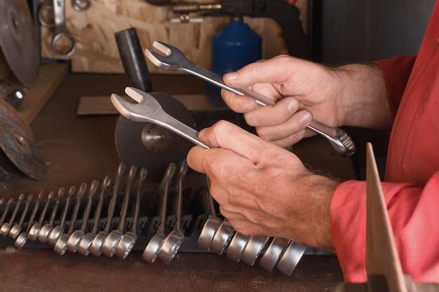 O mestre segura nas mãos duas chaves inglesas de um molho de chaves em uma bancada de trabalho com ferramentas na garagem
