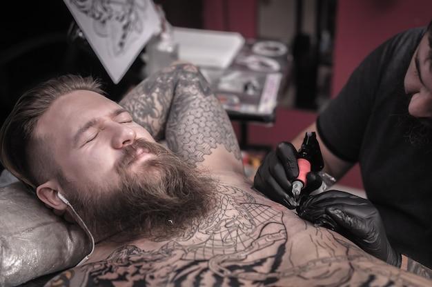 O mestre tatuador faz uma tatuagem no cliente.