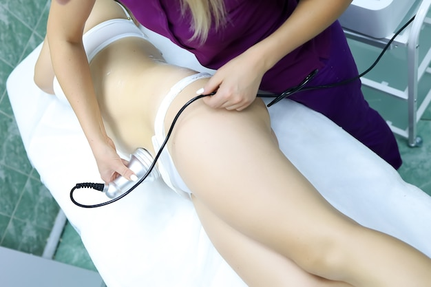 O mestre trabalha com o problema abdominal e remove a celulite com um aparelho ultrassônico