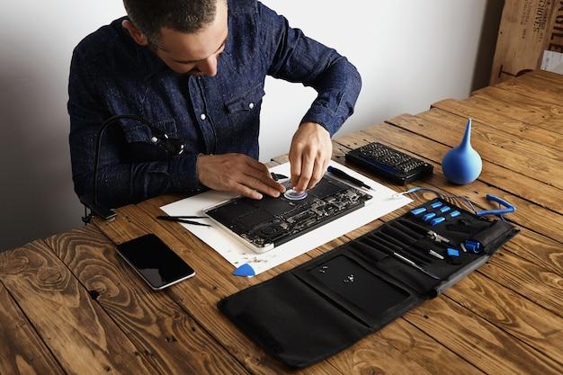 O mestre usa uma pequena ventosa para remover as células da bateria do laptop quebrado para consertá-lo e limpá-lo em seu laboratório com ferramentas especiais na mesa ao redor.