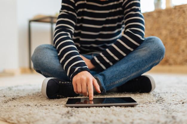 O meu aparelho. adolescente vestindo roupas casuais e tênis, sentado no chão e tocando seu moderno tablet digital sensível ao toque