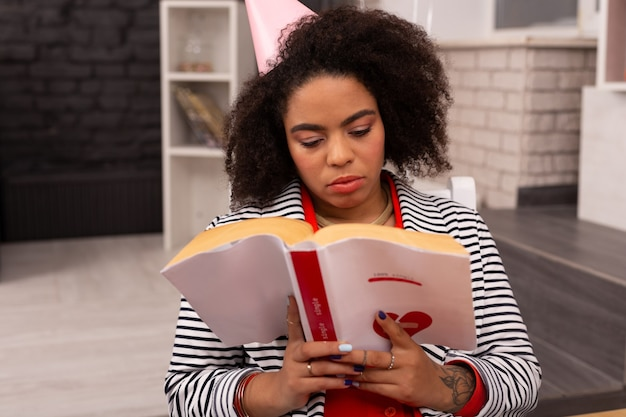 O meu hobby. bela mulher séria lendo um livro enquanto está sentada no café