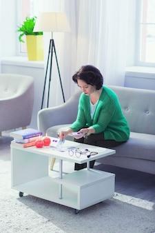 O meu hobby. mulher simpática e simpática olhando as cartas de tarô enquanto quer saber seu futuro