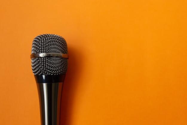 O micrafone musical em uma superfície laranja