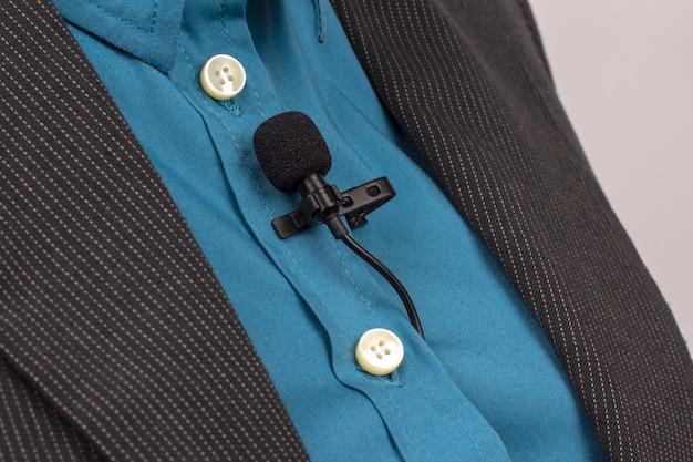 O microfone de lapela é preso com um clipe em azul