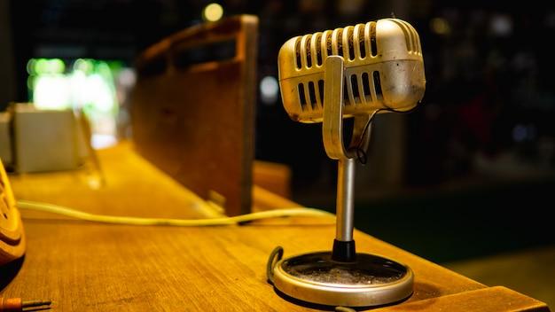 O microfone está localizado em uma mesa de madeira em uma sala de prática de música antiga.