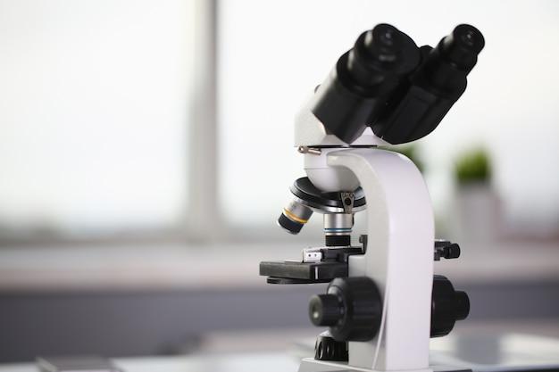 O microscópio de cabeça no laboratório de segundo plano