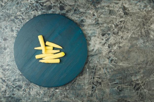 O milho novo em uma placa de madeira redonda na superfície de pedra.