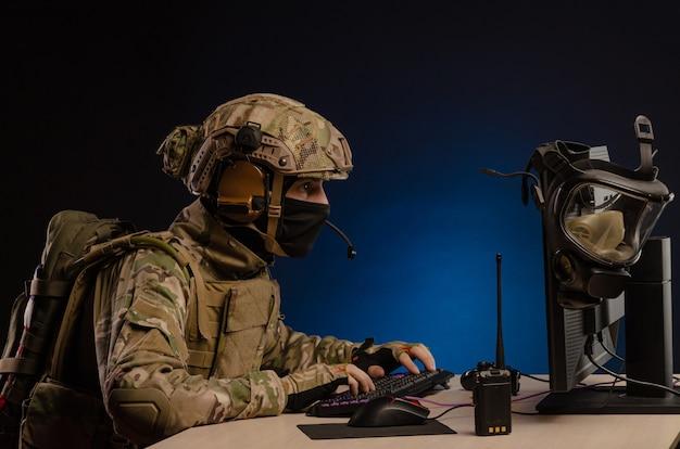 O militar uniformizado sentado em frente a um computador conduz uma guerra cibernética
