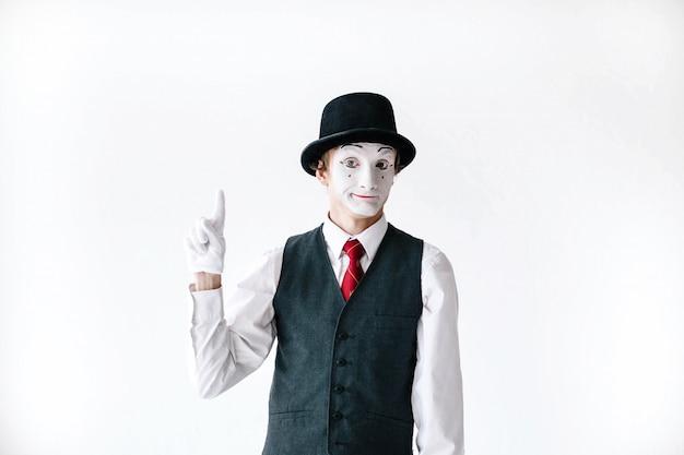 O mime engraçado no chapéu negro prende seu dedo acima