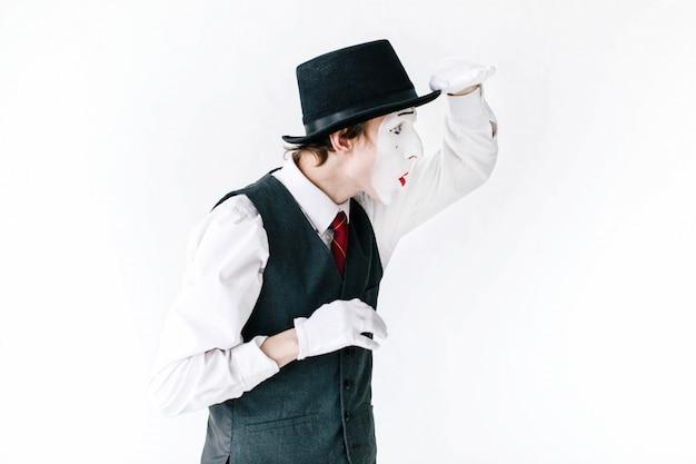 O mime engraçado no chapéu preto olha a maneira distante no fundo branco