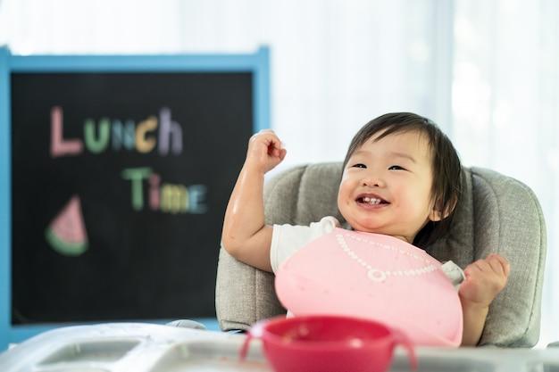 O miúdo bonito novo no assento de alimentação da cadeira alta do bebê que guarda a melancia com cara do sorriso em casa, aprecia comer a fruta doce da refeição e rir a felicidade.