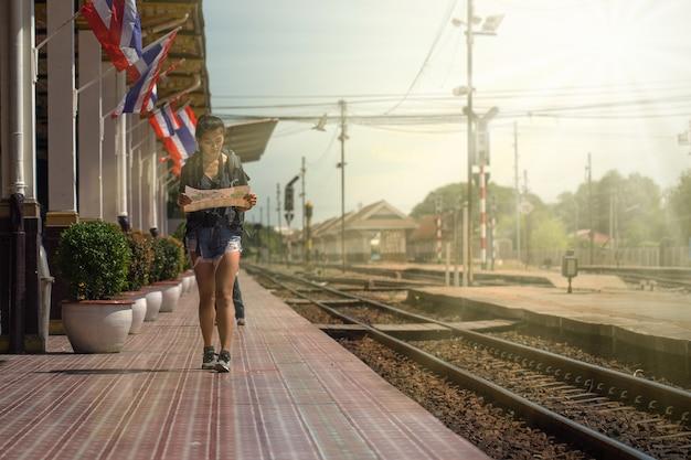 O mochileiro está andando o mapa na estação de trem ao viajar em tailândia.