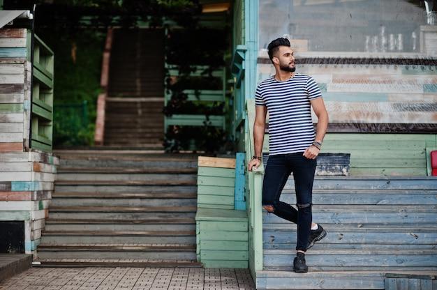 O modelo árabe alto considerável do homem da barba na camisa descascada levantou exterior. cara árabe na moda.
