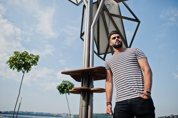 O modelo árabe alto considerável do homem da barba na camisa descascada levantou exterior contra o painel solar. cara árabe na moda.