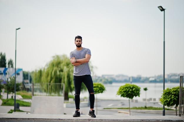 O modelo árabe alto considerável do homem da barba na camisa descascada levantou exterior no parque do skate. cara árabe na moda.