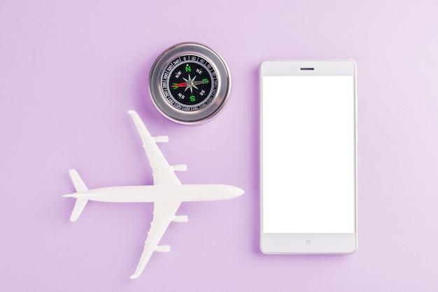 O modelo de avião, bússola e tela em branco do telefone móvel inteligente moderno