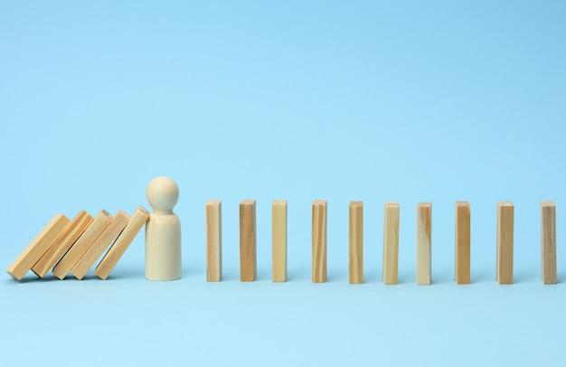 O modelo de madeira de um homem para de cair de barras de madeira em uma superfície azul clara