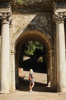 O modelo de menina posa em um arco do antigo edifício