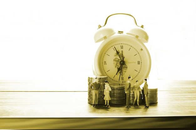 O modelo de pessoas em pé na frente da pilha de moedas com fundo de despertador, conceito de pessoas economizando dinheiro