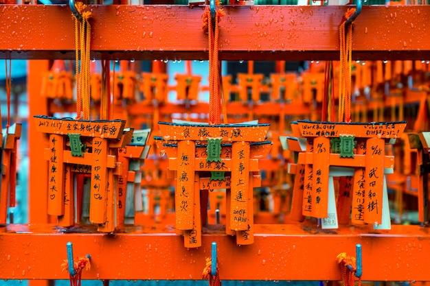 O modelo dos portões torii estava pendurado em um rack depois que um turista os usou para fazer um pedido no santuário fushimi inari, em kyoto.