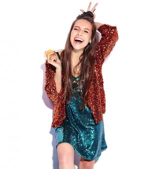 O modelo moreno de sorriso caucasiano bonito da mulher do moderno no revestimento à moda refletindo brilhante brilhante do verão e o vestido verde isolaram-se. comendo biscoito francês