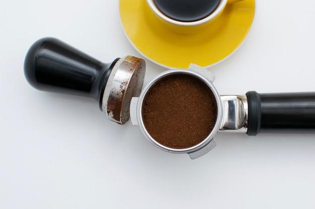 O moedor de café colher e mexer com parte do copo amarelo de café preto